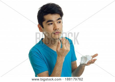 attractive young guy with black hair on his face shaving foam hands close-up isolated on white background