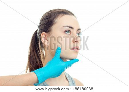 the face of a young cute girls at the beautician who keeps her face with his hand in a blue glove close-up isolated on background.