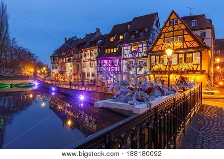 Traditional Alsatian half-timbered houses on the channel in Petite Venise, old town of Colmar, decorated and illuminated at christmas time, Alsace, France