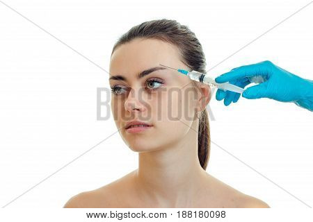 the doctor makes an injection on the forehead at young girl close-up isolated on white background