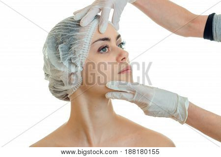 charming young girl came to the doctor in the medical CAP and he checks her face in gloved close-up isolated on the background