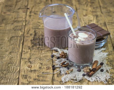 Banana smoothie with chocolate, pear and milk on a wooden table. The concept of a healthy diet.