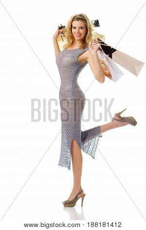young cheerful woman holding shooping bags and looking in camera isolated on white background