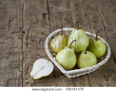 Green pears in basket on rustic brown wooden table. The concept of healthy eating.