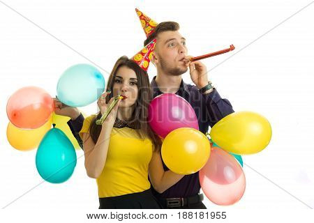 cheerful beautiful wonderful pair celebrate birthday blow horns and carrying a lot of balls is isolated on a white background