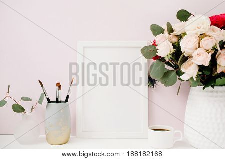Home office desk with photo frame mockup beautiful roses and eucalyptus bouquet in front of pale pastel pink background. Blog website or social media concept .