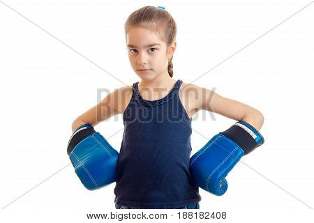 the little girl is standing in a large adult boxing gloves and looking at camera isolated on a white background close-up