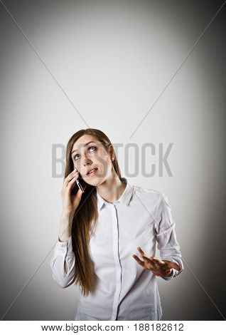 Woman in white is using a mobile phone. Angry woman.