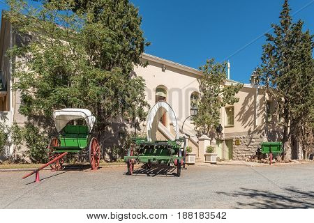An historic ox-wagon and two horse or ox drawn carts in front of the historic station building in Matjiesfontein now a museum