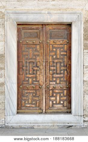 Wooden aged engraved door and exterior stone wall Sultan Ahmet Mosque Istanbul Turkey