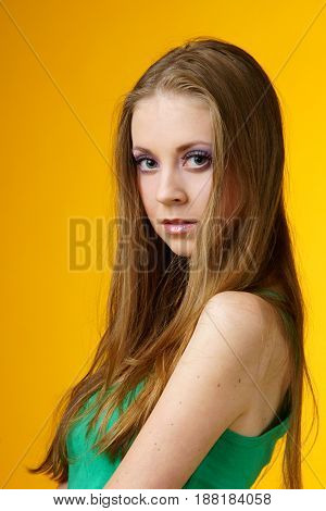 portrait of young pretty woman looking at you on yellow background