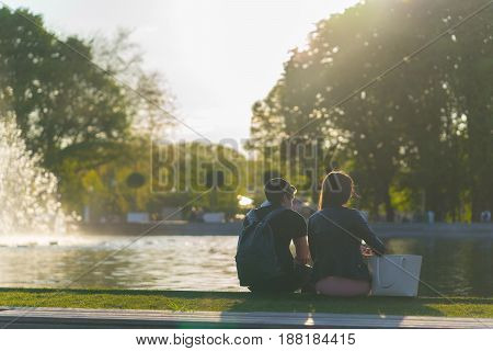 boy and girl sit near fountain on sunset