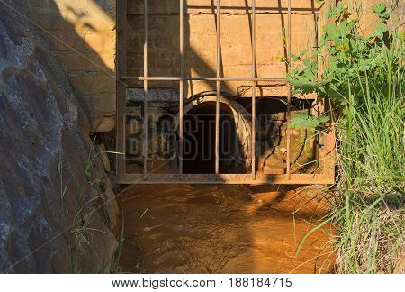 Water runs through the gutter into a pipe fenced with a lattice