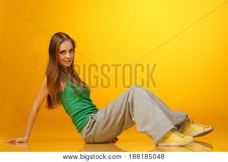 pretty hip-hop girl sitting on yellow background