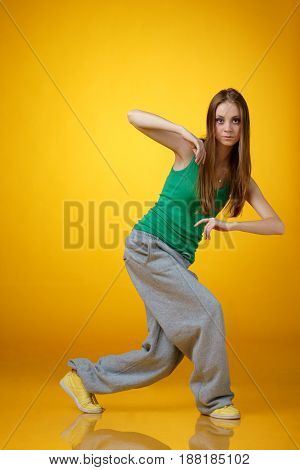 girl dancing hip hop on yellow background