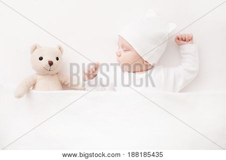 Closeup of New born Baby girl sleeping with her teddy bear. Top view.