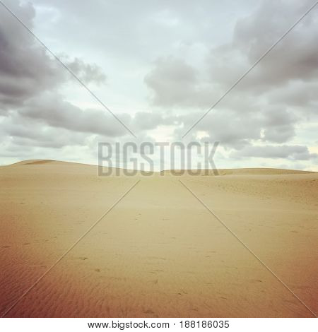 Beautiful landscape with sand dunes and cloudy sky.