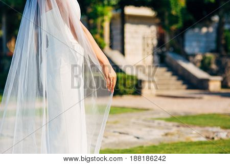 Happy beautiful bride outdoors. Wedding dress fluttering in the wind. Building in the background.