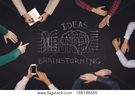 Teamwork concept - top view of six people generate ideasa and brainstorming. Blackboard table.