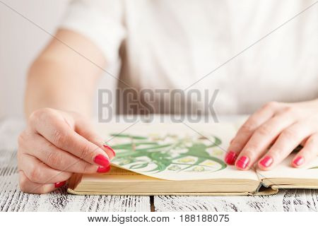 Women hand flipping through a book on table