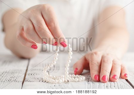 Woman hand with pearl necklace in finger
