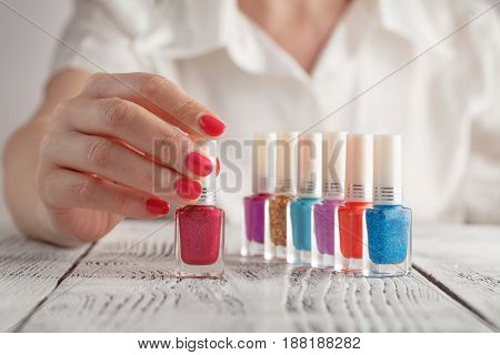 Group Of Bright Nail Polishes Over Wooden Board