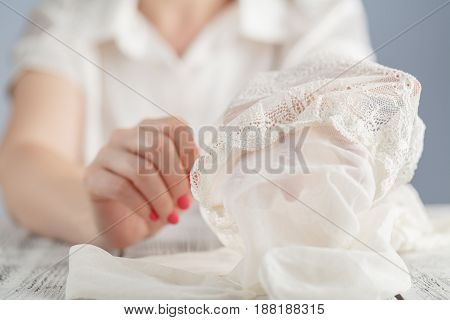 woman check her stockings in hand on table