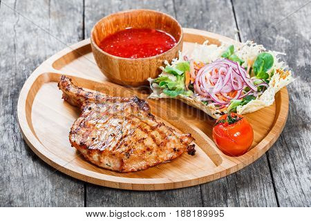 Grilled beef steak on bone fresh salad grilled vegetables and tomato sauce on cutting board on wooden background. Hot Meat Dishes