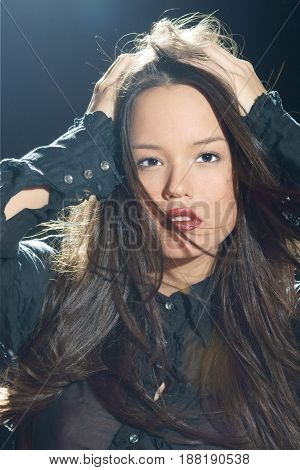 young beautiful woman with magnificent hair in motion and back light on black background
