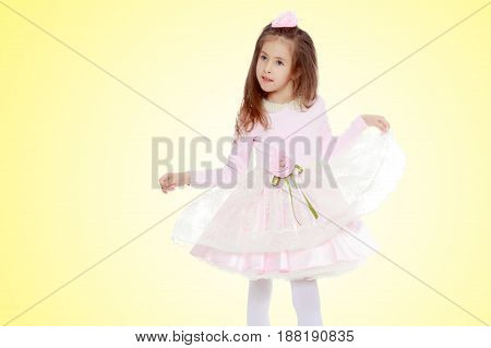 Dressy little girl long blonde hair, beautiful pink dress and a rose in her hair.She plays with her floors for her dress.On a yellow gradient background.