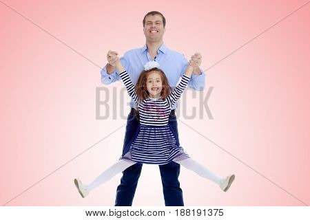 Happy young dad raise his beloved daughter's hands.Pale pink gradient background.