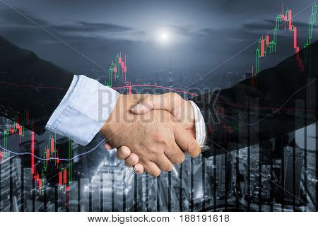 Deal or agreement business concept handshake double exposure cooperation or partnership business with stock exchange market business trading graph in background