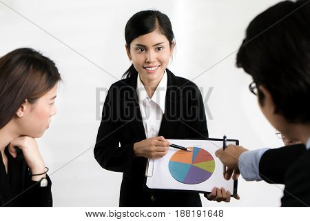 Happy asian businesswoman presenting pile chart to colleagues and attendees have some qustion in the office. Business presentation and meeting concept.