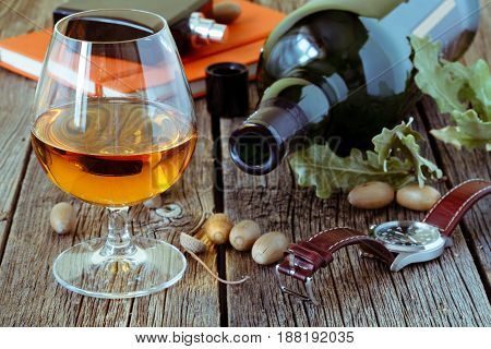 Snifter Of Brandy And Dried Oak Leaves On A Wooden Table