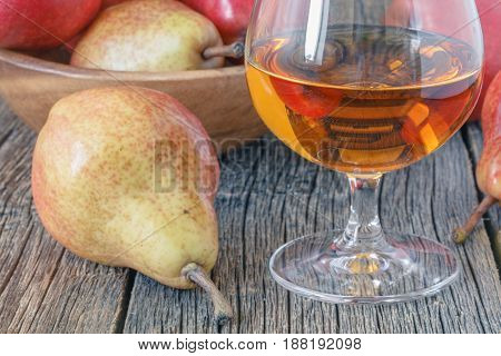 Bottle Of Pear Aguardiente Brandy And Fresh Pear On Rustic Dark Background