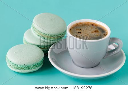 French Macarons And Coffee Cup On Aquamarine Background