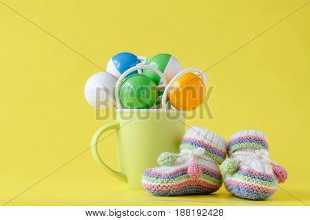 Baby Rattle In Cup On Yellow Background