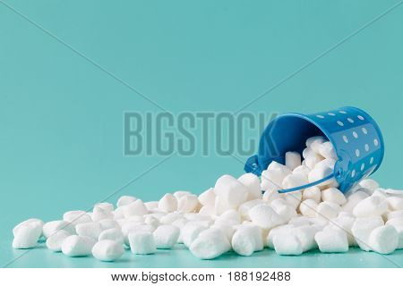 Marshmallows on blue background with copy space.
