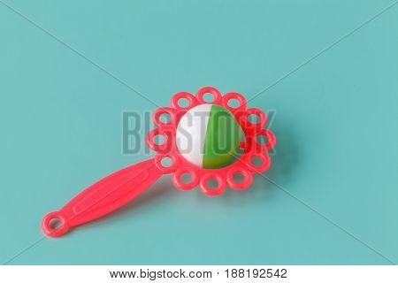 one pink baby rattle on aquamarine background