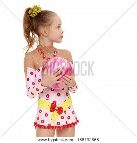 Beautiful little girl gymnast dressed in sports suits for competition, performs exercises with the ball.Isolated on white background.