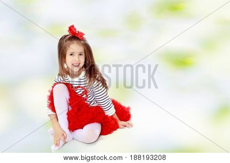 Little girl in a red skirt and bow on her head.She hugged the hand to the knee.Summer white green blurred background.