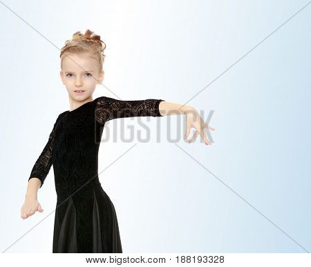 The slender little blonde girl dancer in the long dress of black color made specifically for performing .The girl held out her hands.On the pale blue background.