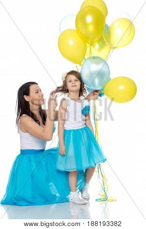 Beautiful mother and daughter in long blue skirts, along with balloons.Mother adjusts her daughter's arm hair.Isolated on white background.