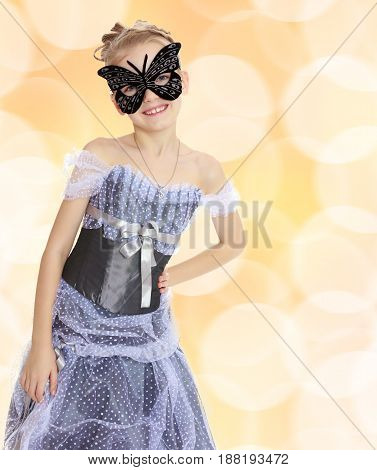 Slender little girl , with beautiful hair on his head, elegant long Princess dress.Posing in carnival mask.