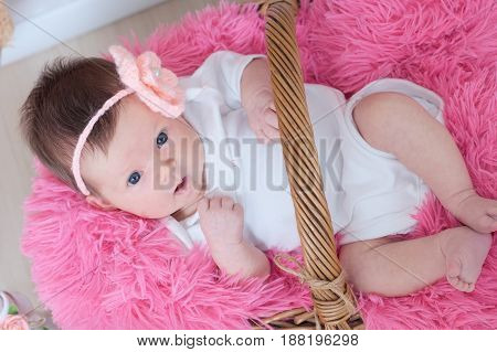 newborn baby girl in pink blanket lying in basket looking at camera with interest. Top view. Infant daughter announcement