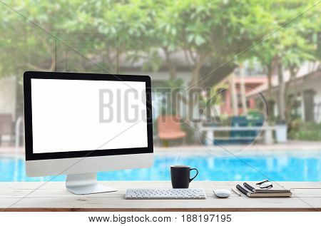 desktop computer on work table and see through resort hotel background