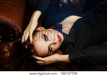 Young attractive girl in a jacket and bow tie. Femme fatale. Evening makeup smokey eye. She is lying on a leather couch and looking up.