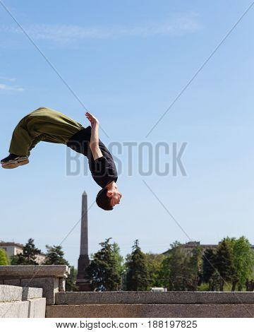 Young man doing a back flip in the background obelisk. Parkour in the urban space. Sports in the city. Sport activity.