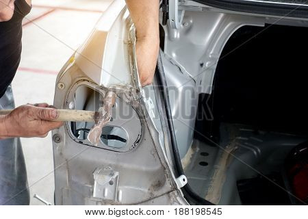 Align metal body car with hammer in automotive industry - auto body repair shop