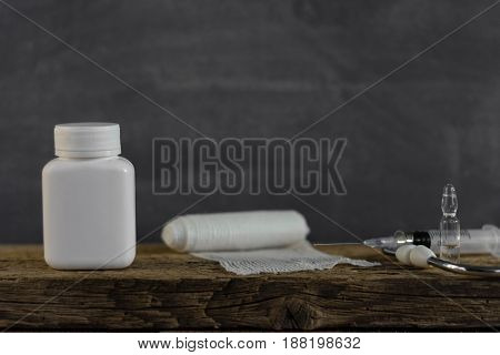 Closed Bottle for pills.Old table.Beautiful dark background.